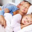 Lovely family sleeping together on bed - Stok fotoğraf