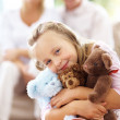 Royalty-Free Stock Photo: Cute little girl with soft toys with her parents sitting at back