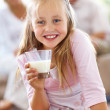 Royalty-Free Stock Photo: Cute girl holding a glass of milk with parents in background