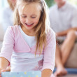Sweet small girl opening gift box with her parents at back - Stock Photo