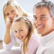 Royalty-Free Stock Photo: Cute young girl sitting with her parents and smiling