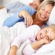 Happy family waking up in the morning on bed - Stock Photo