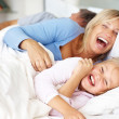 Happy family having fun in morning on bed - Stock Photo
