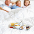 Royalty-Free Stock Photo: Happy young family lying on the bed with breakfast
