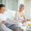 Man reading newspaper while woman preparing breakfast - Stock Photo