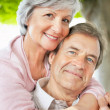 Closeup of a smiling senior woman with arms around a man - Stock Photo
