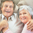 Royalty-Free Stock Photo: Top View of a happy senior couple lying together on the couch