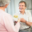 Happy retired man giving woman a present on birthday - Stock Photo