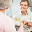 Royalty-Free Stock Photo: Senior man presenting woman a gift for their anniversary