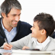 Happy mature father and son doing homework together - Stock Photo