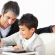 Mature man helping her son to do homework - Stock Photo
