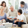 Old man gifting his grandson in presence of their family - Stock Photo