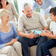 Family looking at happy grandfather gifting his grandson - Stock Photo