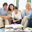 Young boy sitting on sofa with his parents and grandparents - Stock Photo