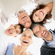Cheerful multi generational family forming a huddle - Stock Photo