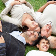 Happy family of five relaxing on grass in park - Stock Photo