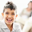 Closeup of a cheerful little boy with parents in the background - Stock Photo