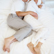 An attractive mature pregnant couple sleeping in bed - Stock Photo