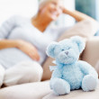 Happy pregnant female with teddy bear - Stock Photo