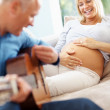 Royalty-Free Stock Photo: Mature man playing guitar for his pregnant wife