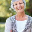 Royalty-Free Stock Photo: Happy senior woman standing with folded hand