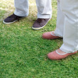 Couple standing together on the green field - 