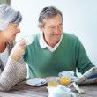 Royalty-Free Stock Photo: Old couple reading newspaper and having breakfast
