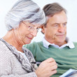 Royalty-Free Stock Photo: Old woman taking notes while sitting with her husband
