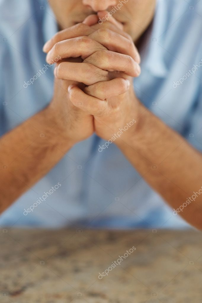 Closeup portrait of a young man praying to god with focus of hands — Stock Photo #3361461