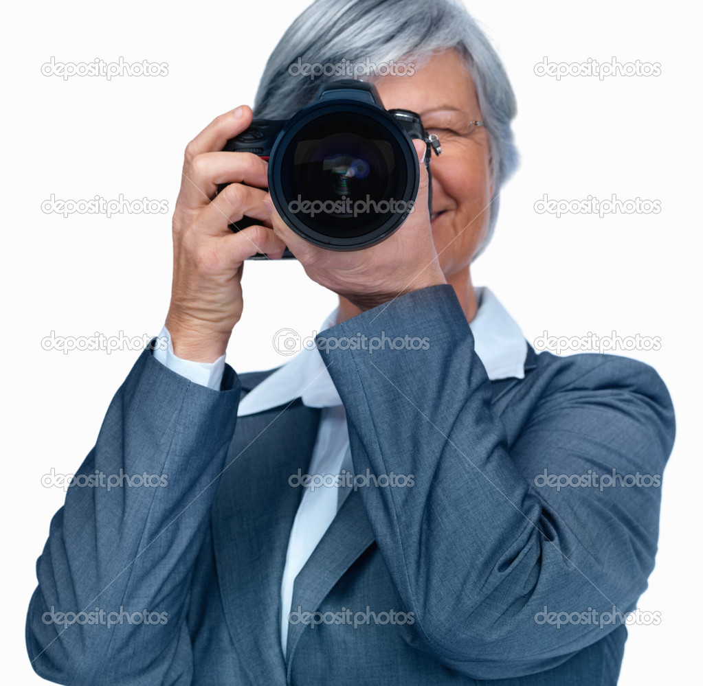 Elderly business woman using a camera while isolated against white  Stock Photo #3361781