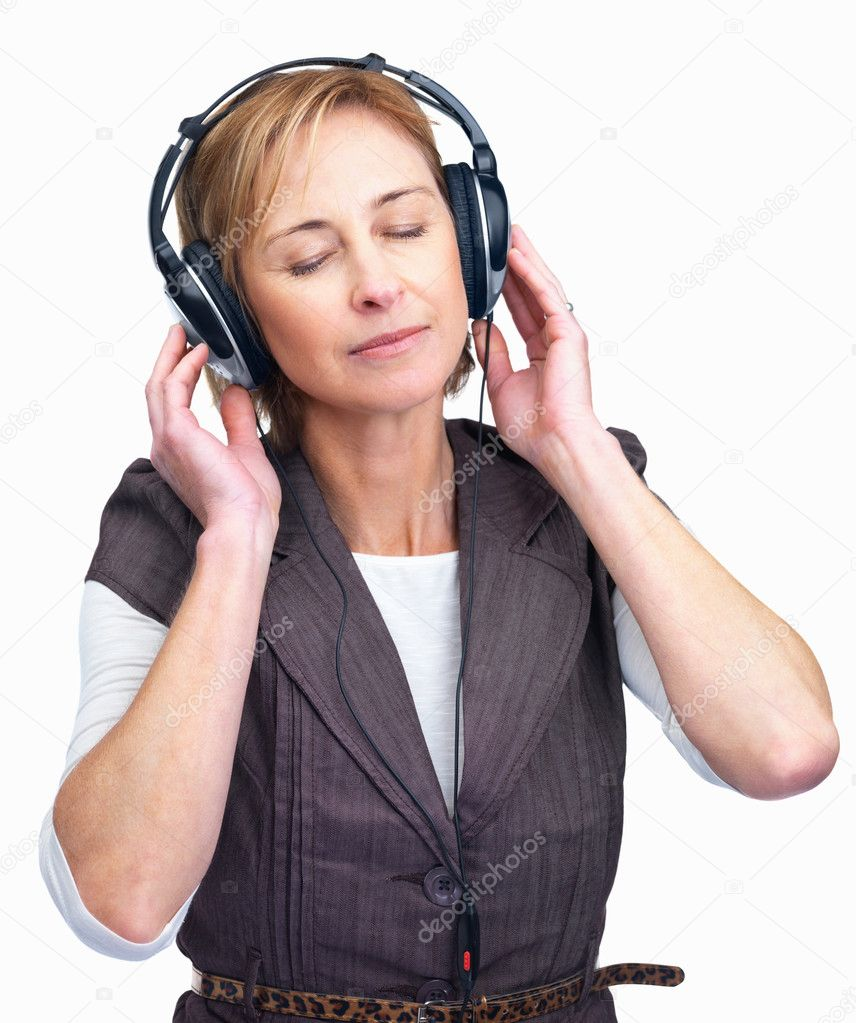 Portrait of pretty mature lady enjoying music on headphones isolated over ...