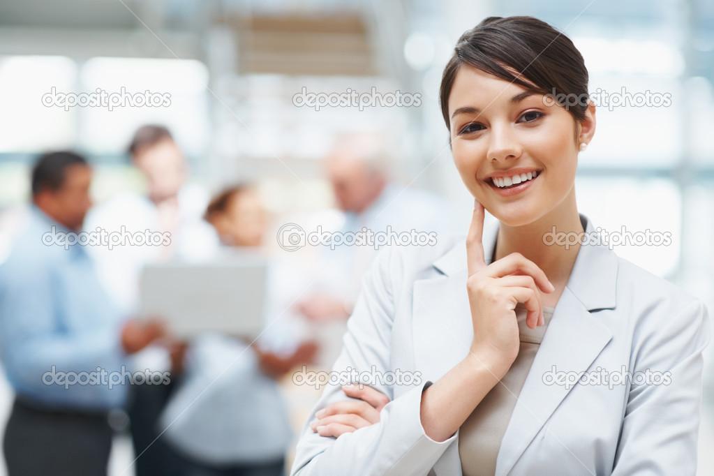 Beautiful young business executive with colleagues discussing in the background — Stock Photo #3365542