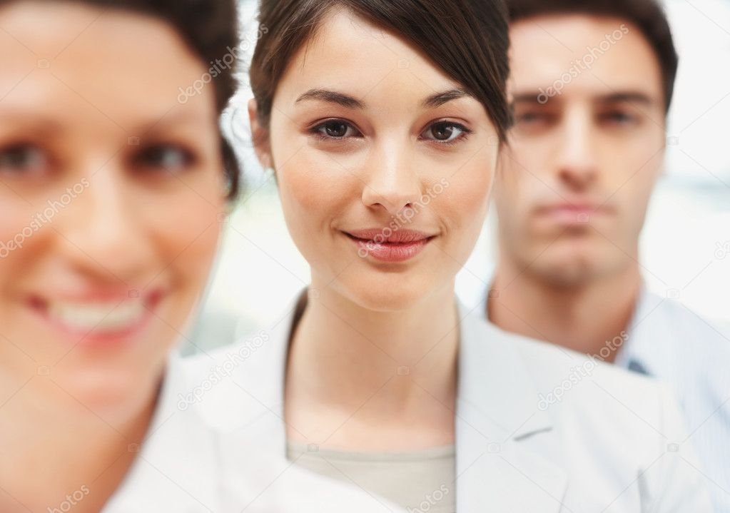 Portrait of a cute young business woman standing in line with colleagues — Stock Photo #3365835