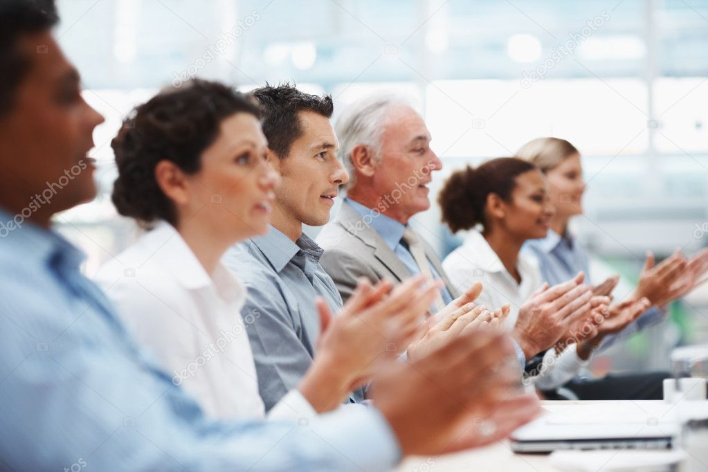 Multi ethnic coworkers sitting in a line and applauding at conference table — Stock Photo #3366182