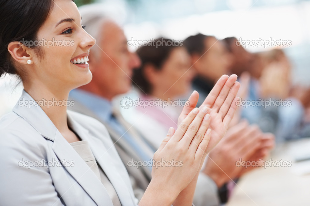 Pretty young business woman with colleagues applauding at a seminar — Stock Photo #3366205