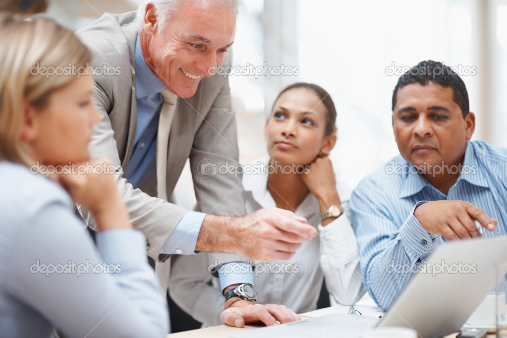 Senior business manager discussing a new project on laptop with colleagues — Stock Photo #3366237