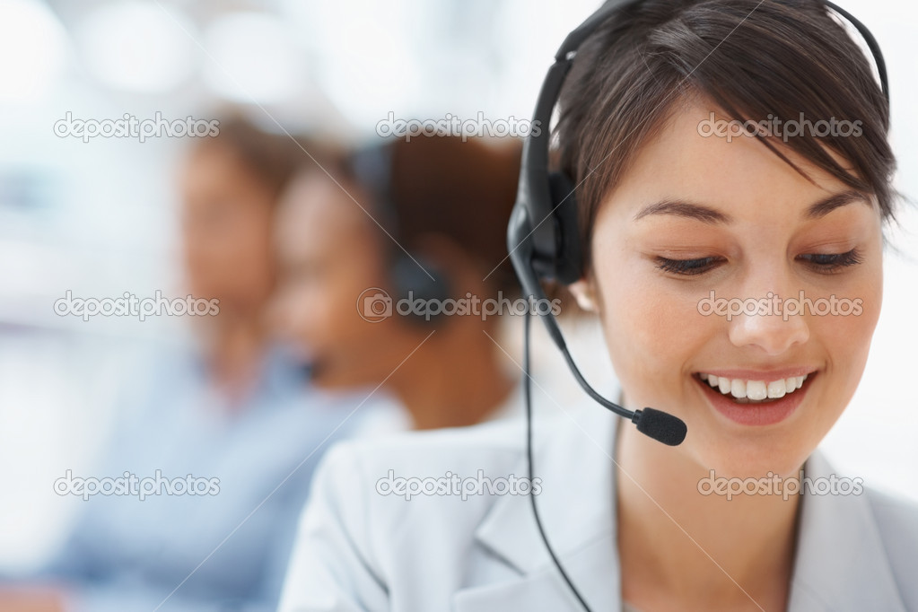 Beautiful customer representative with headset smiling during a telephone conversation — Stock Photo #3366263
