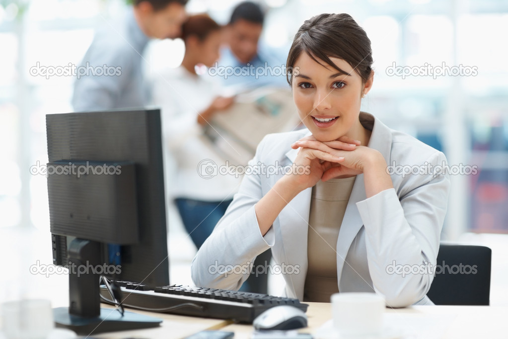 Pretty Caucasian business woman at office desk with colleagues in the back  Foto de Stock   #3366293