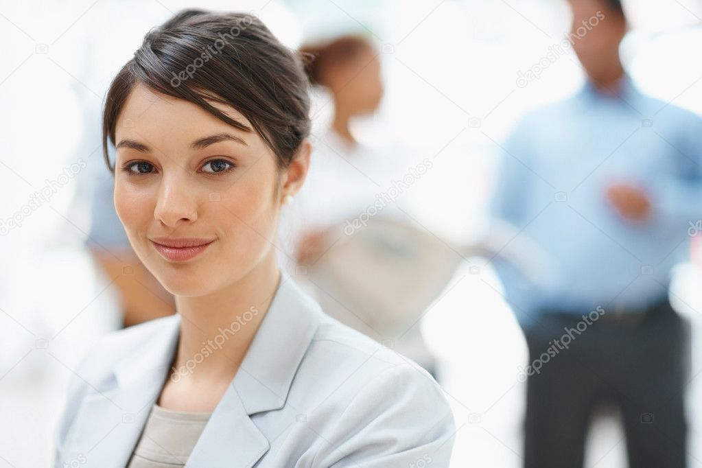 Portrait of a successful business woman smiling with colleagues in the back — Stock Photo #3366311