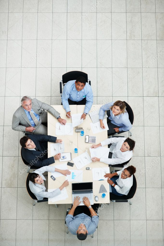 Top view of business sitting at a table for a meeting and looking upwards  Stock Photo #3366410