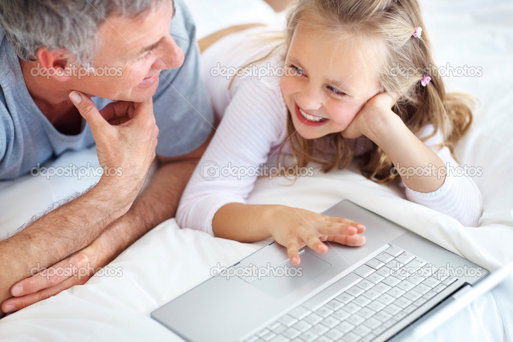 Portrait of happy young girl using laptop with her father  Stock Photo #3368205
