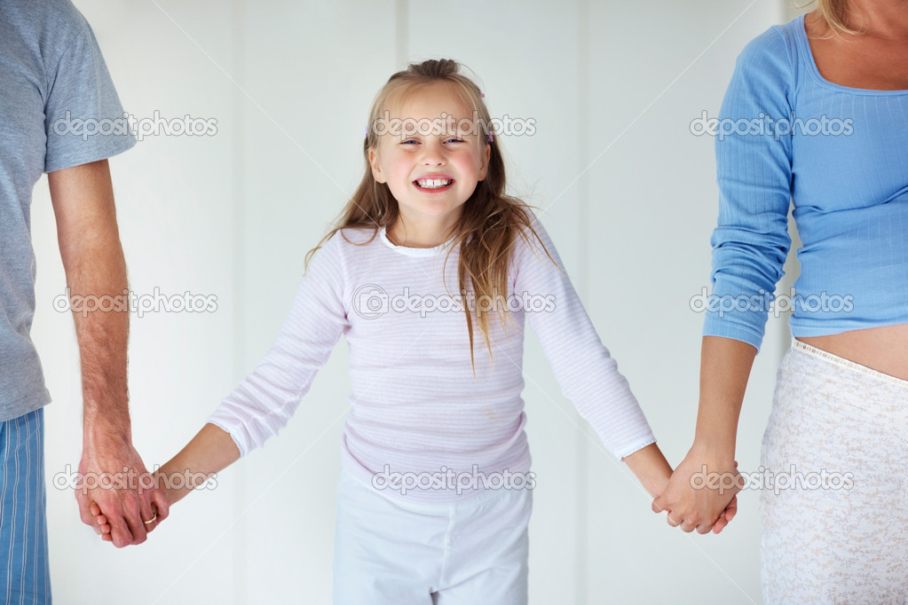 Portrait of sweet young girl holding hands of her parents — Stock Photo #3368223