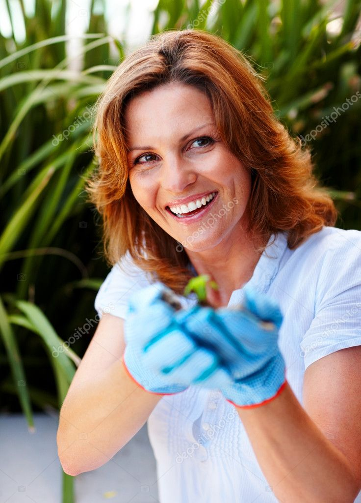 Portrait of woman holding a young plant in a garden - Outdoors  Stock Photo #3368355