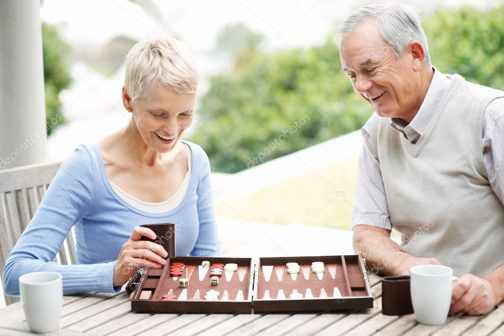 Cheerful senior man and woman enjoys a game of backgammon — Stock Photo #3368660