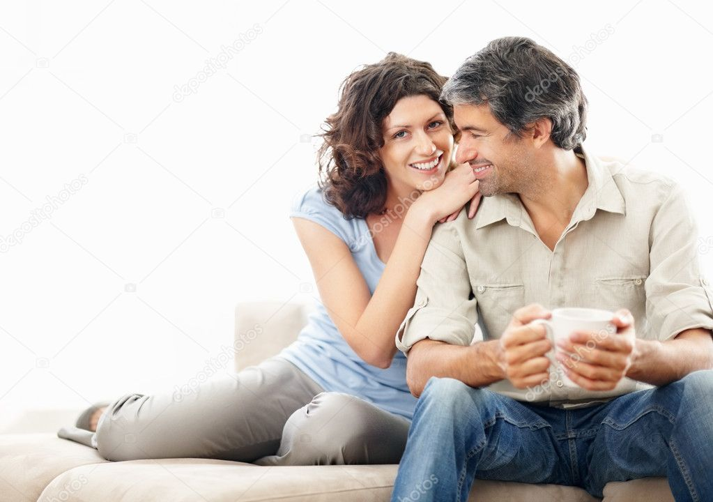 Portrait of a smiling cosy middle aged couple on couch by lots of copyspace — Stock Photo #3368697