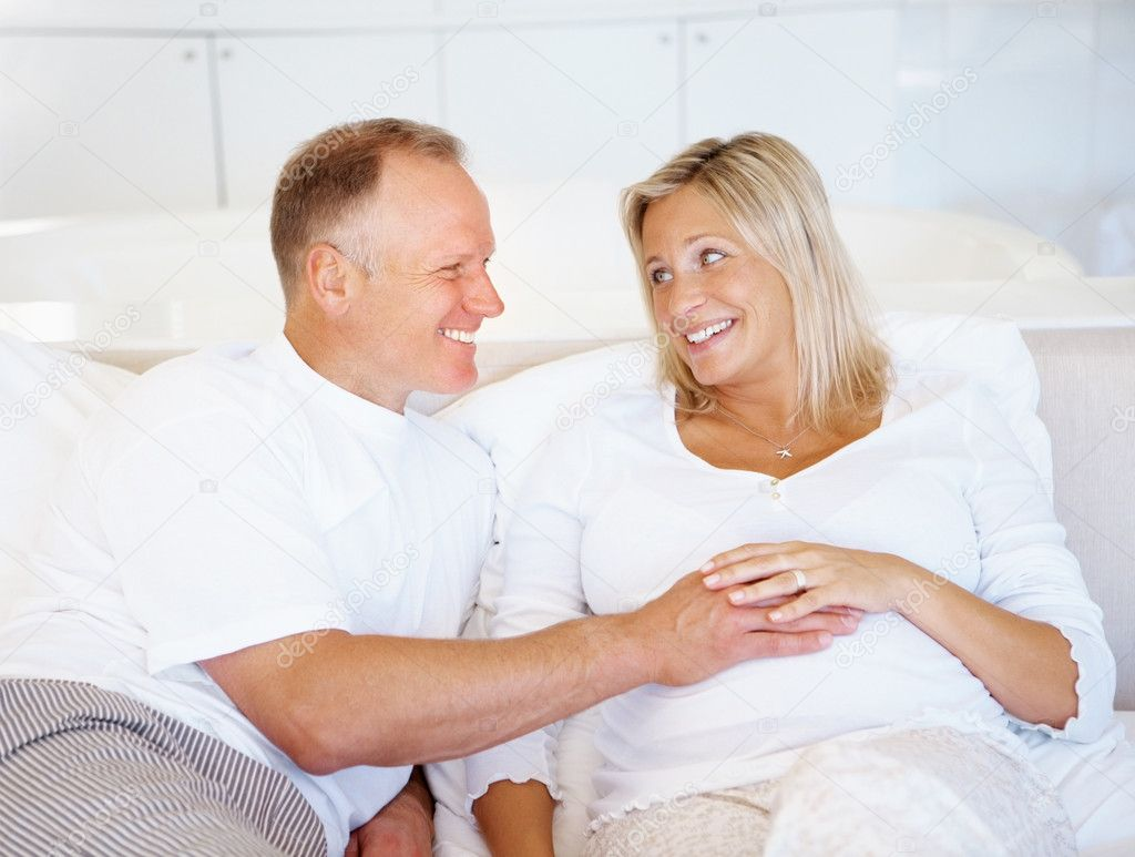 Portrait of a happy middle aged man touching his pregnant wife tummy — Stock Photo #3368725