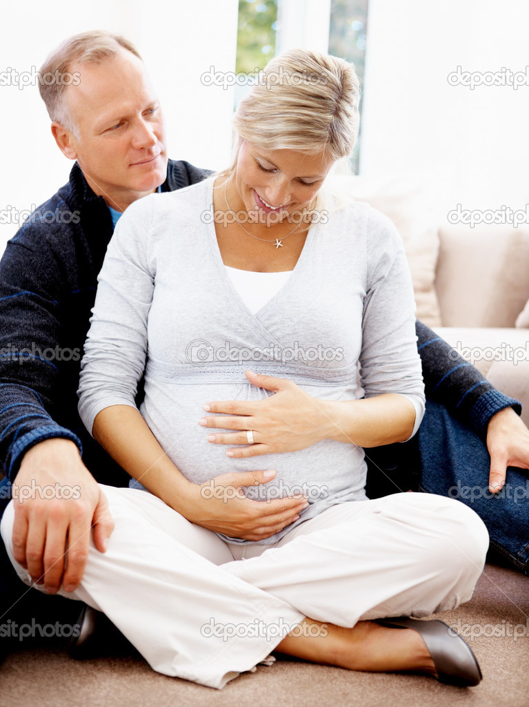 Portrait of a happy mature pregnant woman with her husband while sitting on the floor at home  Stock Photo #3368770