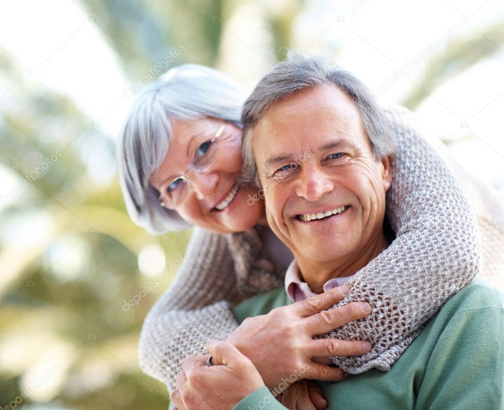 Closeup portrait of smiling mature couple together in the park - Outdoor