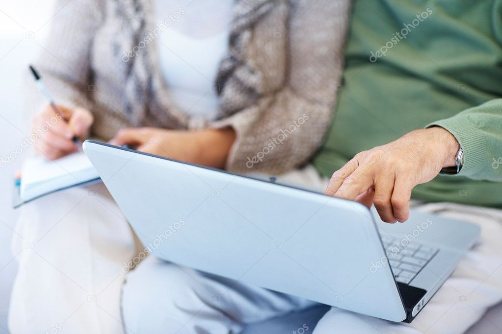 Cropped image of a retired old couple extracting information from laptop — Stock Photo #3369184