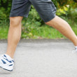 Young athlete running, focus on legs - Stock Photo